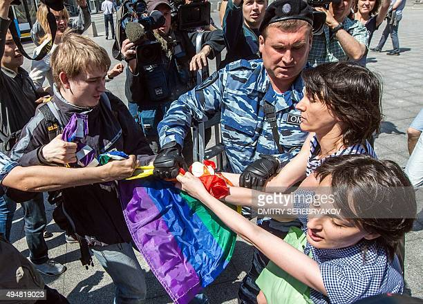 A man takes away a rainbow flag as a policeman detain gay rights activists during their protest in central Moscow on May 31 2014 Riot police on May...