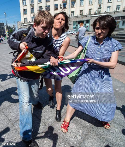 A man takes away a rainbow flag during a protest called by gay rights activists in central Moscow on May 31 2014 Riot police on May 31 arrested two...