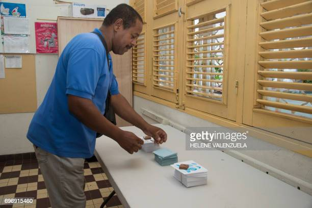 A man takes ballots during the secound round of the French legislative elections at a polling station in PointeaPitre on June 17 2017 / AFP PHOTO /...