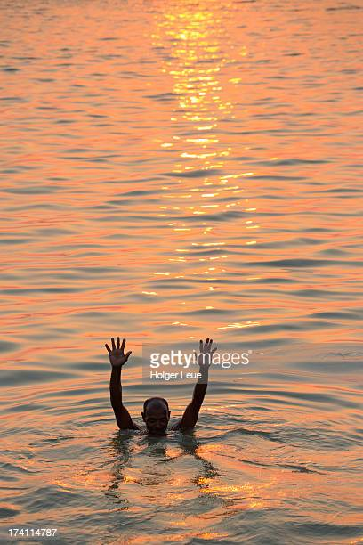 Man takes bath in Ganges river at sunset