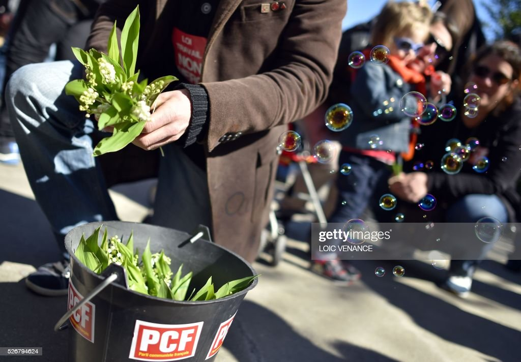 A man takes bits of lily of the valley in a bucket with a French Communist Party sticker during the traditional May Day rally in Nantes, western France, on May 1, 2016. / AFP / LOIC