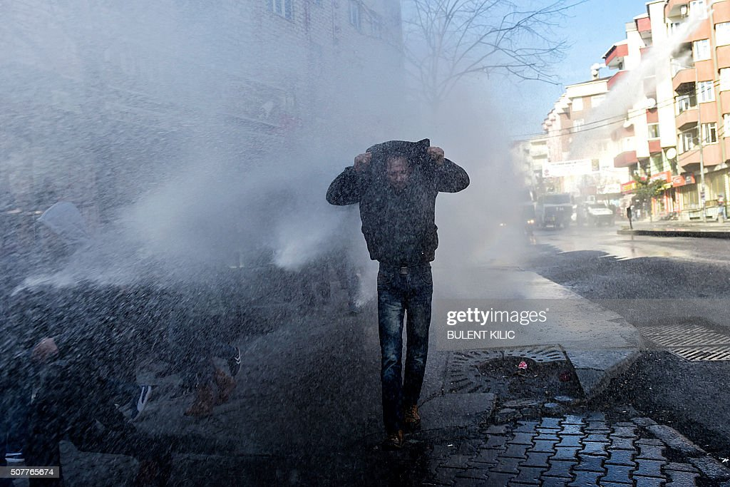 TOPSHOT A man takes cover as Turkish police spray water cannon to disperse demonstrators who gathered in Istanbul to protest curfews in eastern...