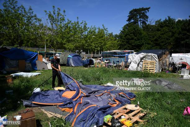 A man takes down a tent as the Valmy migrant camp set up outside the Stade des Alpes in Grenoble is evacuated on May 24 2017 The occupants of the...