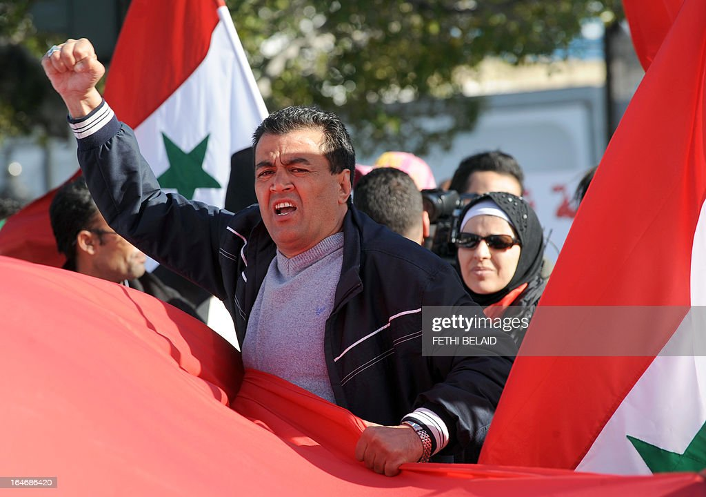 A man takes part in a global anti-capitalist event to demand a more just world order in the center of Tunis after the opening of the World Social Forum (WSF) on March 26, 2013. More than two years after the Jasmine revolution, tens of thousands of people are expected for the WSF, dubbed the forum of 'dignity', a watchword of the Tunisian uprising that inspired revolts across the Arab world. AFP PHOTO/FETHI BELAID