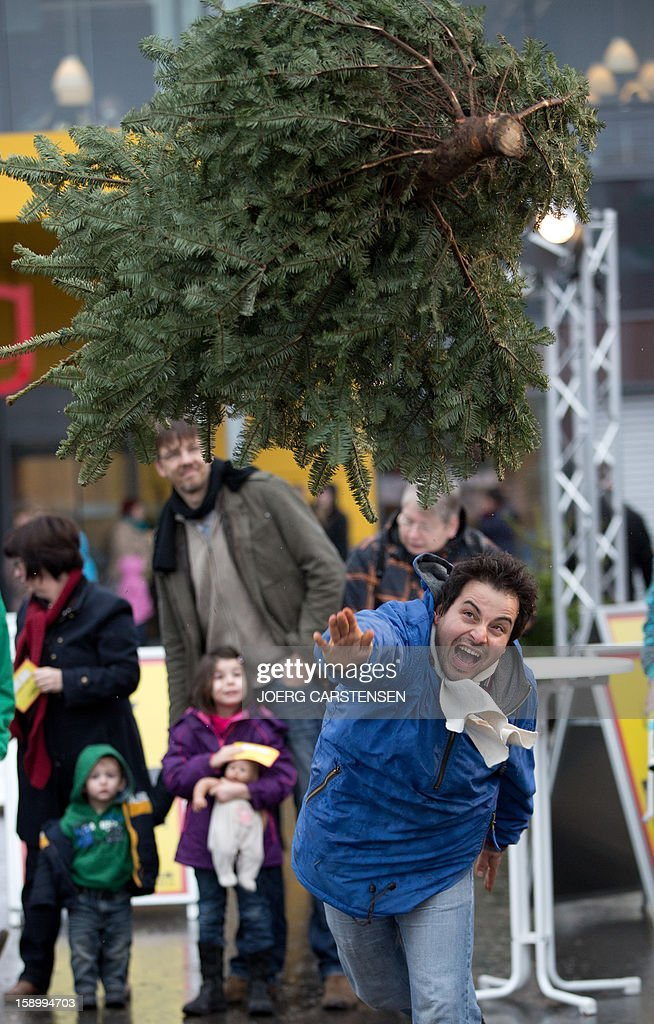 A man takes part in the 'Knut Christmas Tree Throwing Championship' on January 5, 2012 in Berlin.