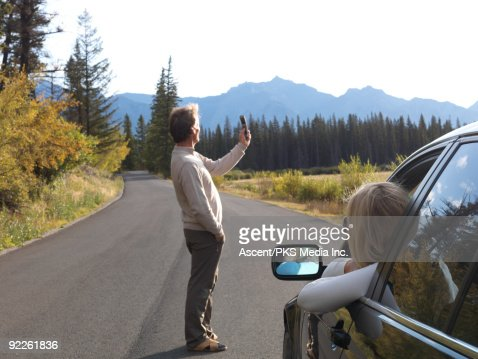 Man takes photo with cell phone while woman waits : Stock Photo