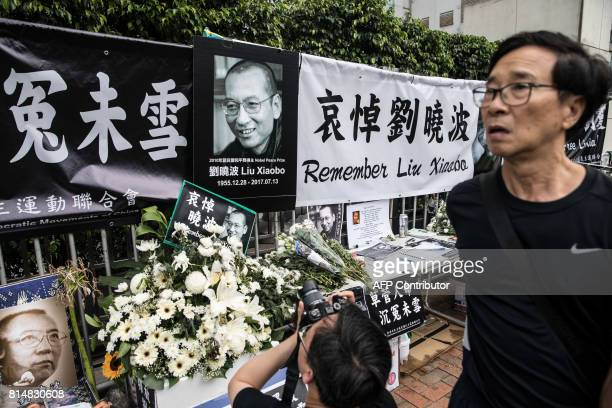 A man takes photographs at a makeshift memorial for the late Chinese Nobel laureate Liu Xiaobo outside the Chinese Liaison Office in Hong Kong on...