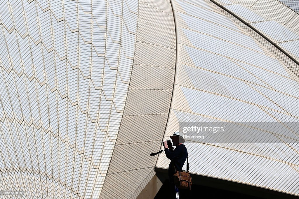 A man takes photographs in front of the Sydney Opera House in Sydney, Australia, on Monday, Dec. 24, 2012. At least 150,000 people from mainland China and across Asia are projected to descend on Sydney, Australia's most populous city, during the New Year's Eve and Chinese New Year period. Photographer: Brendon Thorne/Bloomberg via Getty Images