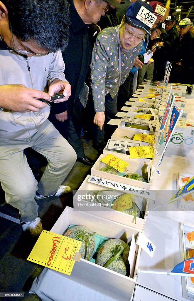 A man takes photographs of the 1.6 million price tag (bottom) which a box of a pair of Yubari Melon fetched 1.6 million Japanese yen in the first auction of the season at Sapporo Central Wholesale Market on May 24, 2013 in Sapporo, Hokkaido, Japan. The highest hammer price was 2.5 million for a pair of orange-fleshed melon in 2008.