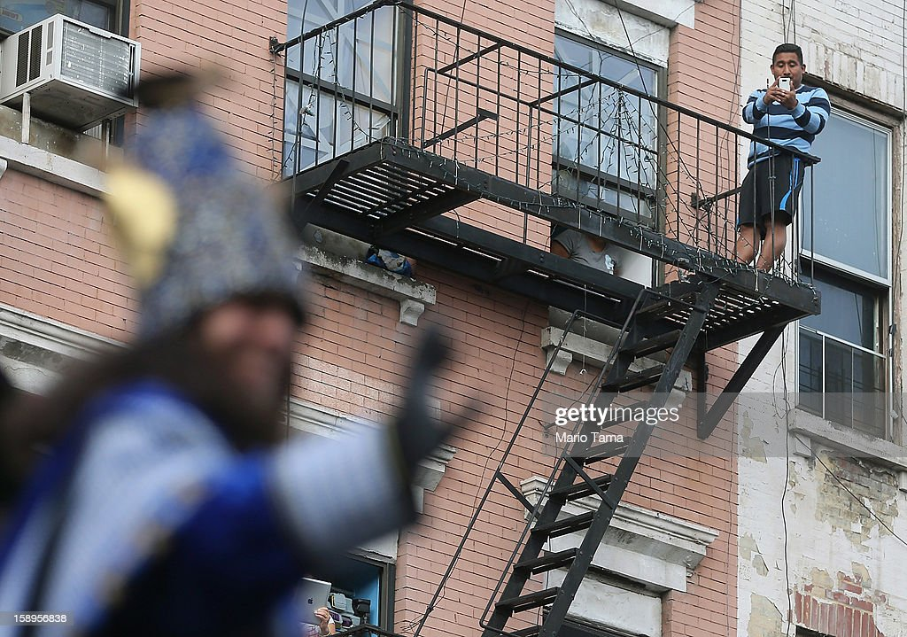 A man takes photos from a fire escape as revelers pass during the Three Kings Day Parade in East Harlem on January 4, 2013 in New York City. The parade celebrates the Feast of the Epiphany, also known as Three Kings Day, marking the Biblical story of the visit of three kings to Bethlehem to visit the baby Jesus, revealing his divinity.