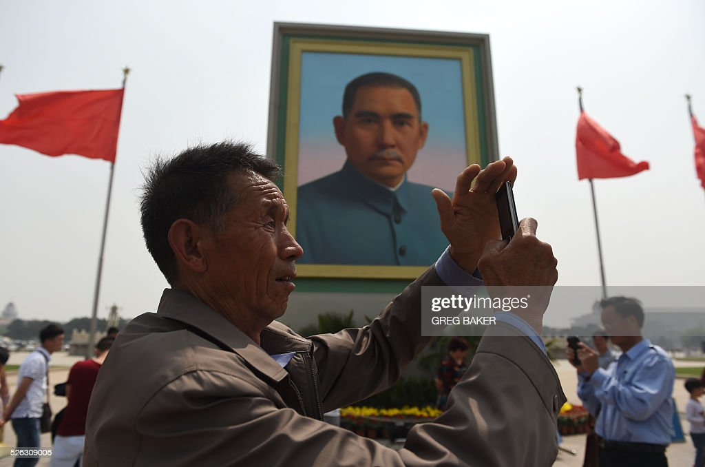 A man takes photos in front of a portrait of Sun Yat-sen in Beijing's Tiananmen Square on the eve of May Day on April 30, 2016. Sun is considered the founding father of modern China after his 1911 overthrow of imperial rule by the Qing Dynasty. / AFP / GREG