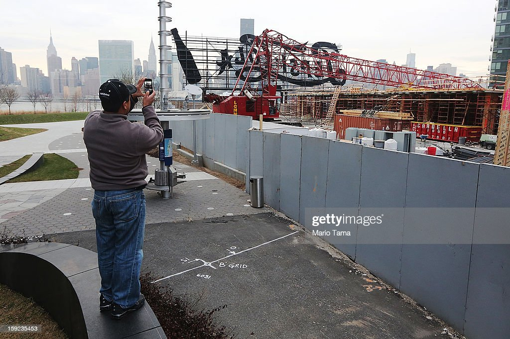 A man takes photos of a construction crane after it collapsed on January 9, 2013 in the Queens borough of New York City. The crane collapse injured seven construction workers on the site in the Long Island City neighborhood.