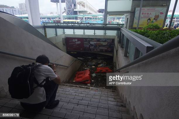A man takes photos of a flooded underground walkway which links to the opposite side of a main road in Macau on August 24 after Typhoon Hato hit the...