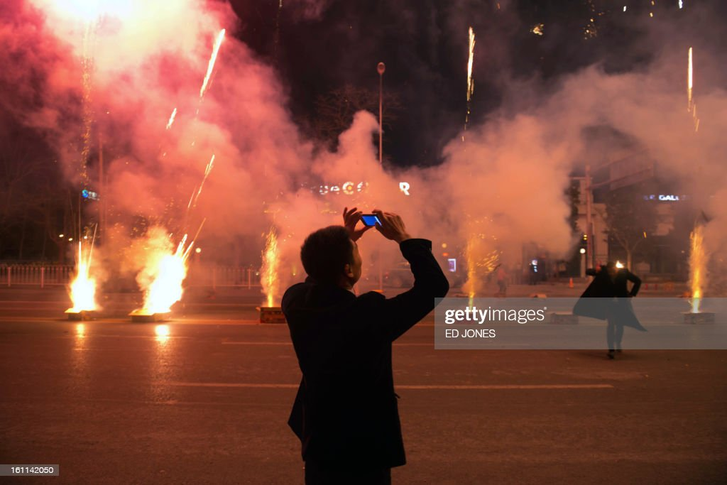 A man takes photos of fireworks on a street in Beijing on February 10, 2013. Revellers across the city lit fireworks as China welcomed the lunar new year of the snake. AFP PHOTO / Ed Jones