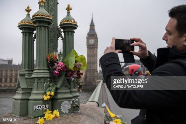 A man takes photos of floral tributes on Westminster Bridge opposite the Houses of Parliament in London on March 24 2017 two days after the March 22...