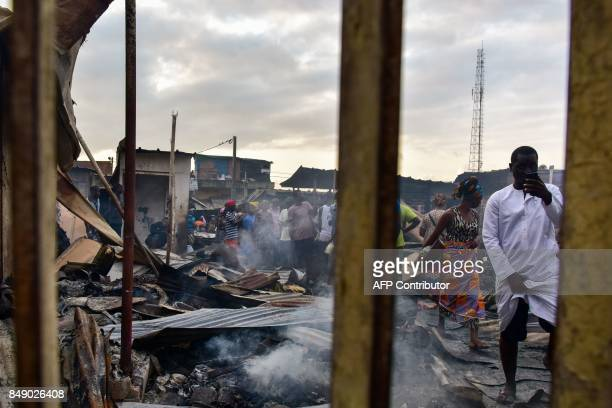 A man takes photos with a mobile phone as sellers walk through debris in a market after a fire devastated the building overnight on September 18 2017...