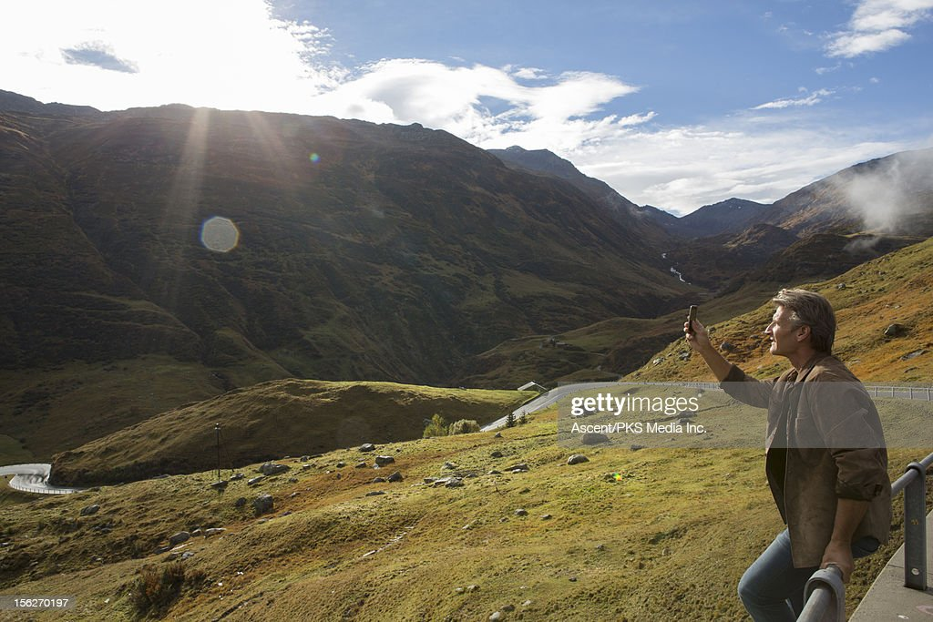 Man takes picture by roadside, near Furka Pass : Stock Photo