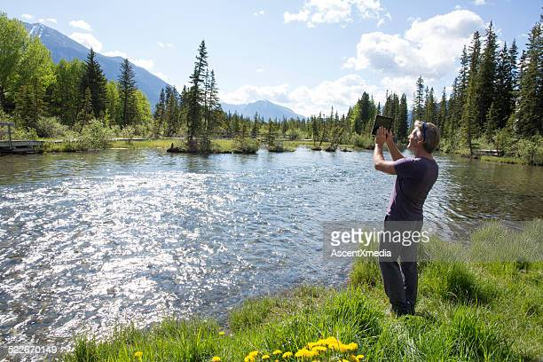 Man takes picture from bank of mountain creek