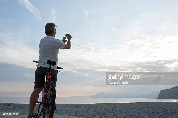 Man takes picture from bicycle saddle, out to sea