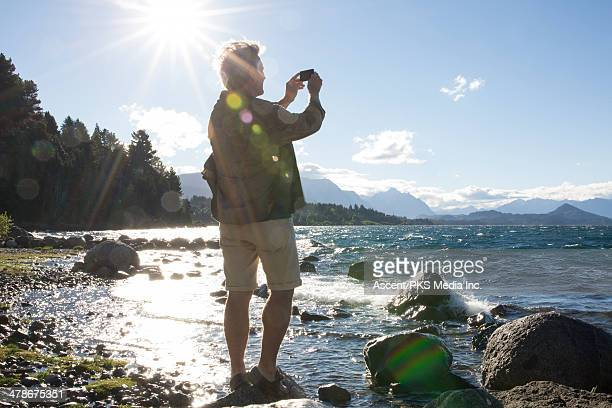 Man takes picture from rock near lake edge