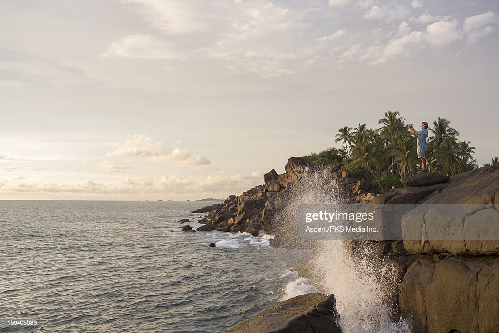 Man takes picture from sea cliff, as surf crashes : Stock Photo