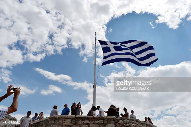 A man takes picture of a Greek flag atop the Acropolis archaeological site on August 23 2015 Greek opposition parties try to form a coalition...