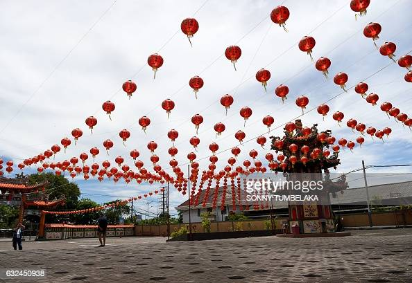 A man takes picture of lanterns decorating a Chinese temple ahead of the Lunar New Year festival in Denpasar on Indonesia's Bali island on January 23...