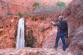 Man with photo gear takes picture of Mooney Falls with his mobile phone, Havasu Canyon, Arizona, USA