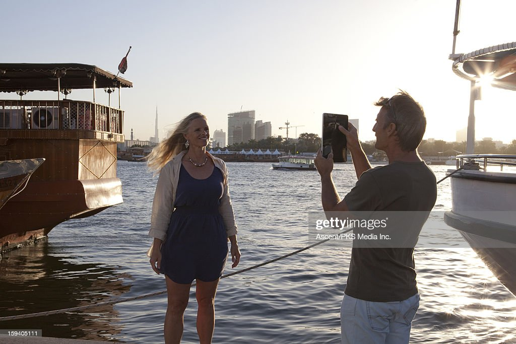 Man takes picture of woman in front of Dubai River : Stock Photo