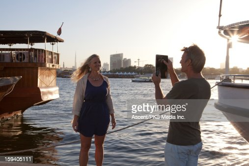 Man takes picture of woman in front of Dubai River : Stockfoto