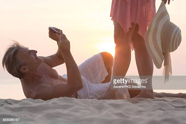 Man takes picture of woman on beach, ground level