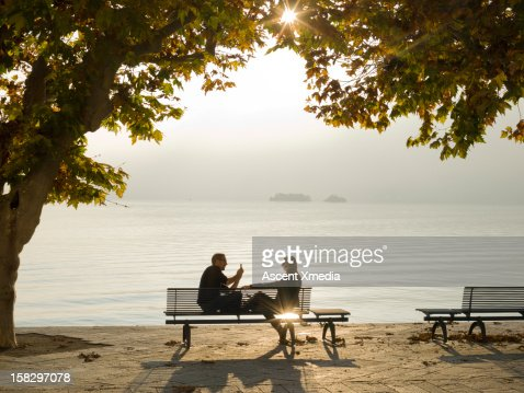 Man takes picture of woman on bench, lake edge : Stock Photo