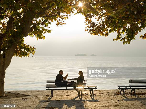 Man takes picture of woman on bench, lake edge