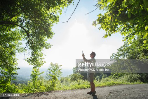 Man takes picture on forest road, digital tablet : Stock Photo