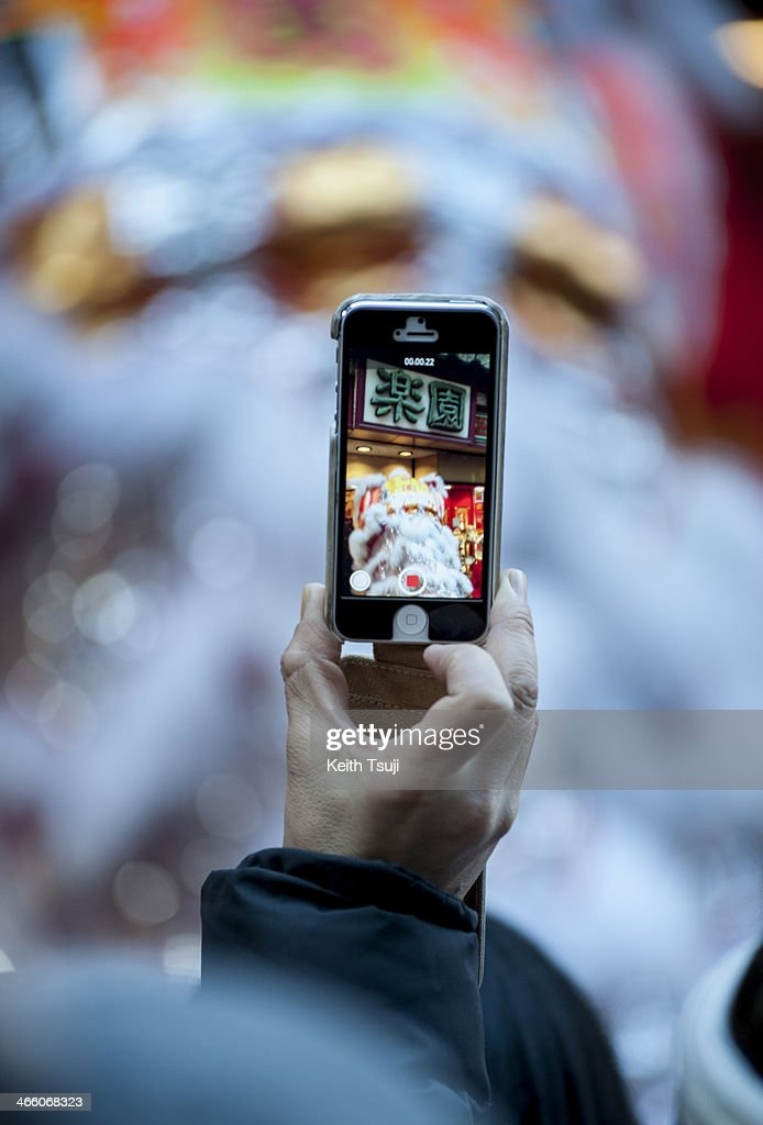 A man takes picture with his smartphone during a lion dance performance in the Yokohama China Town on January 31, 2014 in Yokohama, Japan. It's the Lunar New Year and Year of the Horse, Chinese New Year is an important traditional Chinese holiday and it is celebrated worldwide within the Chinese community.