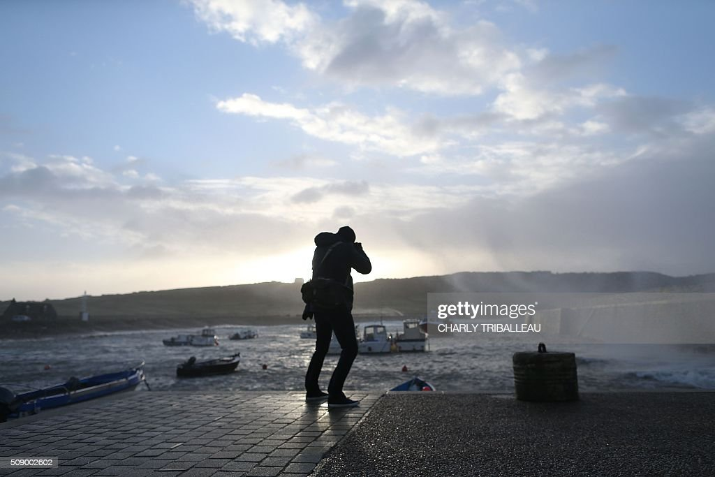 A man takes pictures at the harbour in Auderville, northwestern France, on February 8, 2016, as strong winds hit the region. Winds of over 130 kh/h were recorded in the region where 16 departments have been placed under alert for wind and flooding waves. / AFP / CHARLY TRIBALLEAU