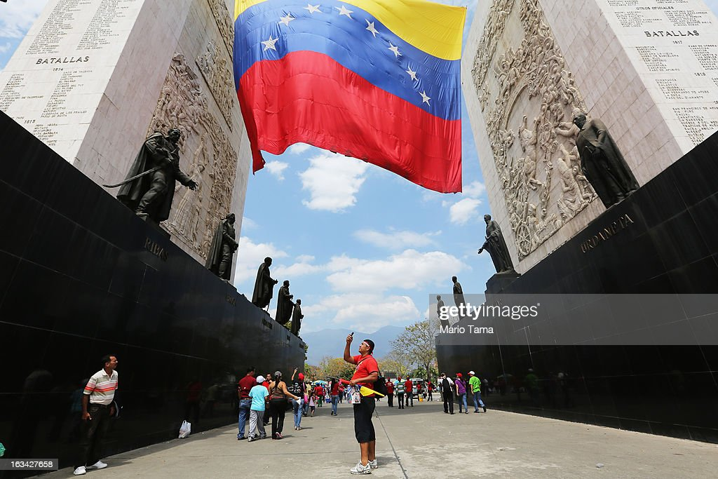 A man takes pictures beneath statues of national heroes near where others wait to view the body of deceased Venezuelan President Hugo Chavez outside the Military Academy on March 9, 2013 in Caracas, Venezuela. Venezuelans continue to wait in line for hours to pay their last respects to Chavez on the day after his funeral. Venezuela's elections commission has set April 14 as the date for voting to replace the late Chavez.