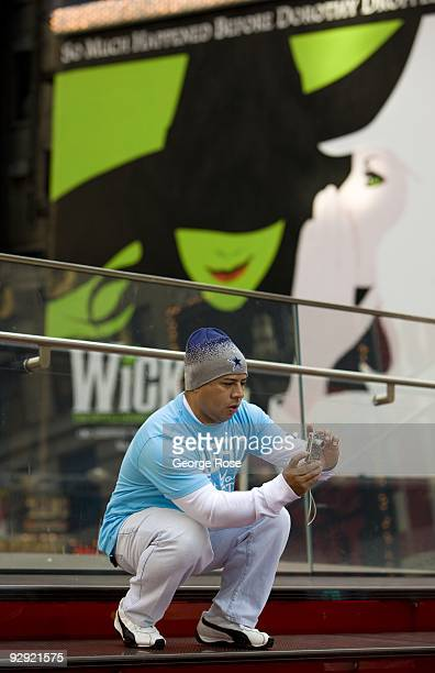 A man takes pictures in Times Square as seen in this 2009 New York NY early evening cityscape photo