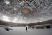 A man takes pictures inside the crumbling oval skeleton of the House of the Bulgarian Communist Party on mount Buzludzha in central Bulgaria on March...