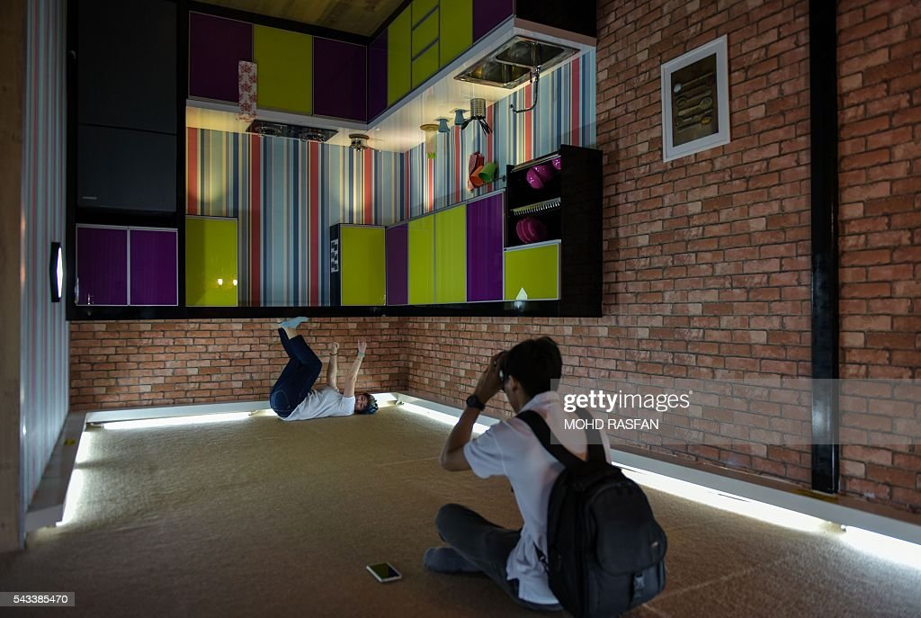 A man (R) takes pictures inside the Kuala Lumpur Upside Down House at KL Tower in Kuala Lumpur on June 28, 2016. Kuala Lumpur Upside Down House is a two-storey house and is the latest attraction for tourists arriving to the Malaysian capital where everything inside such as the furniture are placed in an upside down position. / AFP / MOHD