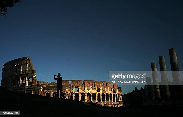 A man takes pictures near the Colosseum at sunset on November 21 2014 in Rome AFP PHOTO / FILIPPO MONTEFORTE