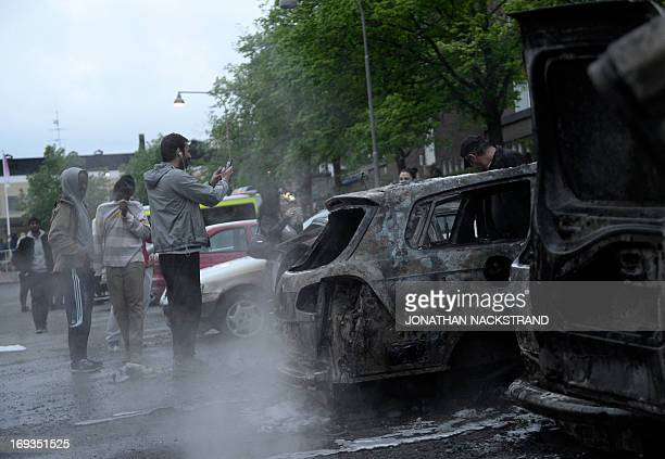 A man takes pictures of a car gutted by fire in the Stockholm suburb of Rinkeby after youths rioted in several different suburbs around Stockholm...