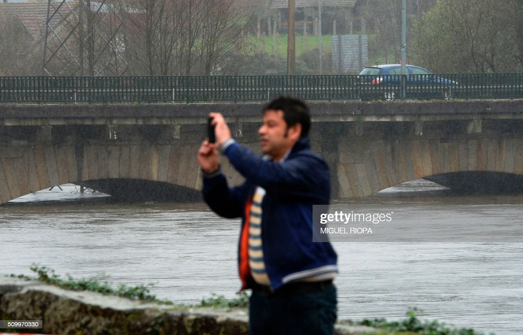 A man takes pictures of a flooded area next to the river Tea in Ponteareas, northwestern Spain, on February 13, 2016. / AFP / AFP or licensors / MIGUEL RIOPA