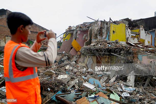 A man takes pictures of a house demolition at Kalijodo redlight district Bulldozers started demolishing hundreds of buildings in the Indonesian...