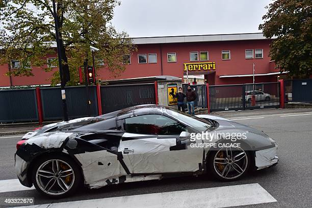 A man takes pictures of a prototype of the Italian car maker Ferrari which enters the Ferrari factory on October 18 2015 in Maranello Fiat Chrysler...