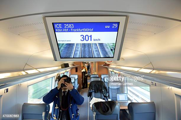 A man takes pictures of a screen with the speed indicator during a ride on the latest generation of the ICE 3 Deutsche Bahn highspeed train version...