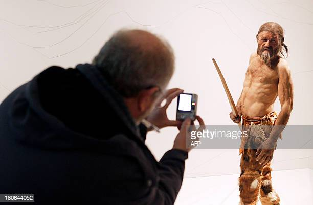 A man takes pictures of a statue representing an iceman named Oetzi discovered on 1991 in the Italian Schnal Valley glacier is displayed at the...