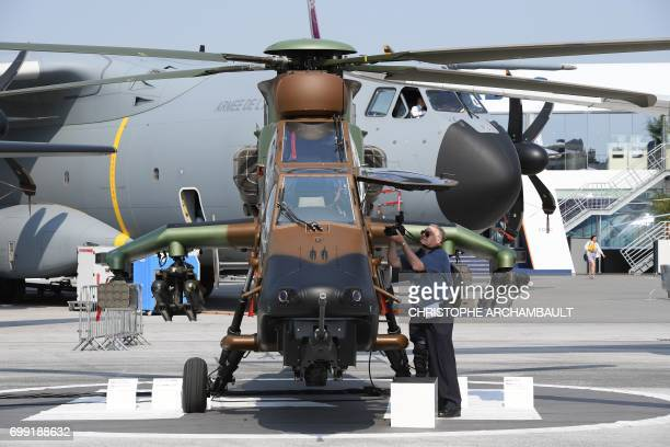 A man takes pictures of an Airbus Tiger helicopter at the International Paris Air Show in Le Bourget outside Paris on June 21 2017 / AFP PHOTO /...