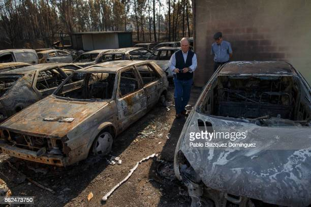 A man takes pictures of burnt cars at a cars repair workshop on October 17 2017 in Tondela Portugal At least 41 people have died in fires in Portugal...