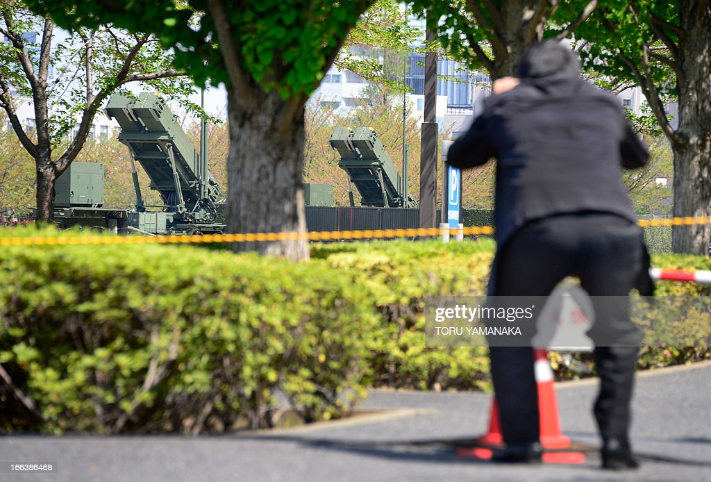 A man takes pictures of Patriot Advanced Capability-3 (PAC-3) missile launchers (back) deployed at the Defence Ministry in Tokyo on April 12, 2013. Japan on April 12 remains on full alert over a possible North Korean missile launch with Patriot missile batteries positioned in and around its teeming capital city. AFP PHOTO/Toru YAMANAKA